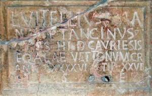"L VITELLIVS MANTAI F TANCINVS CIVES HISP CAVRIESIS EQ ALAE  VETTONVM C R ANN XXXXVI STIP XXVI H S E  ""Lucius Vitellius Tancinus, hijo de Mantai, un ciudadado de España, de Caurium (Coria), tropa del Ala Vettona, Ciudadanos de Roma, de 46 años con 26 años de servicio. Aquí descansa."" (RIB 159; tombstone)"